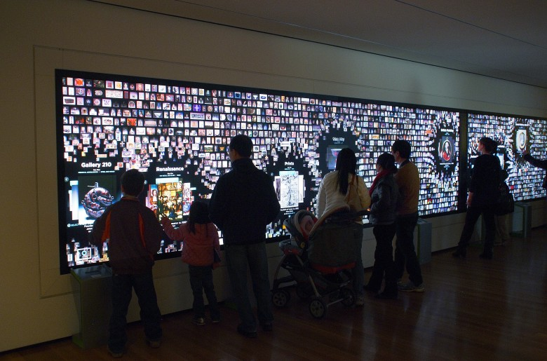 Visitors interact with the 'Collection Wall' in its collection view mode