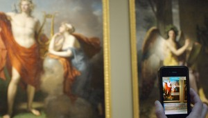 Visitor photographs a painting from app on her iPhone