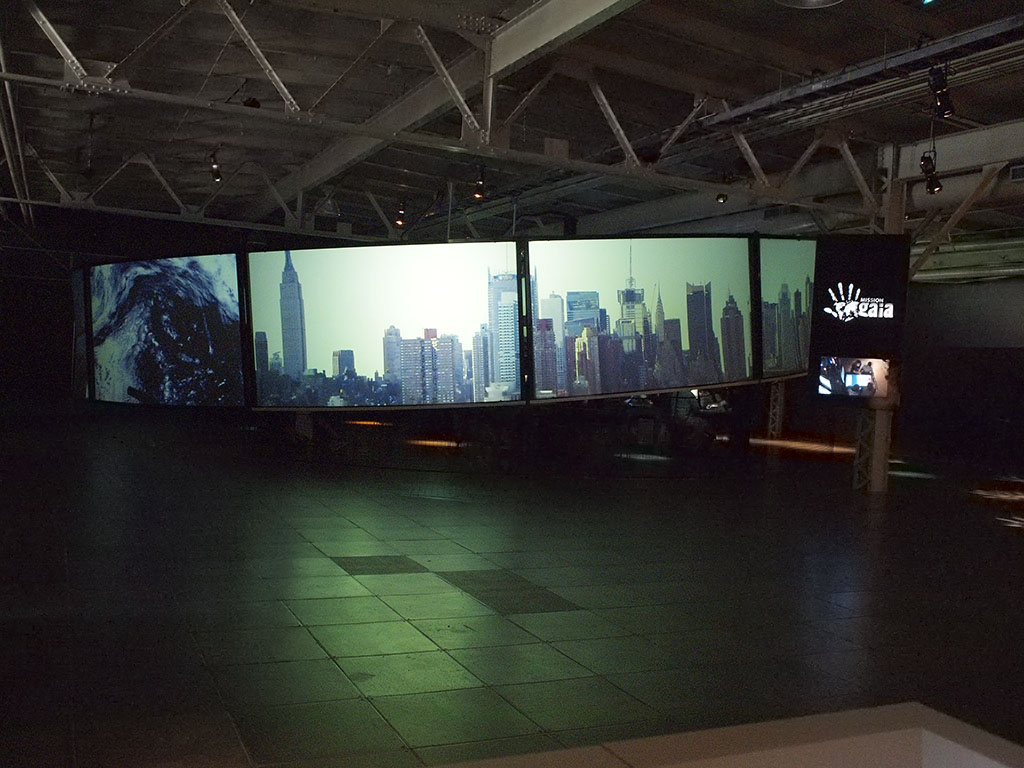 Dark industrial space with wide row of screens, city skyline images projected