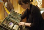 Curator Raewyn Passmore removes coins from shipwreck display / La conservatrice Raewyn Passmore retire les pièces de monnaie d'un présentoir d'objets tirés d'une épave