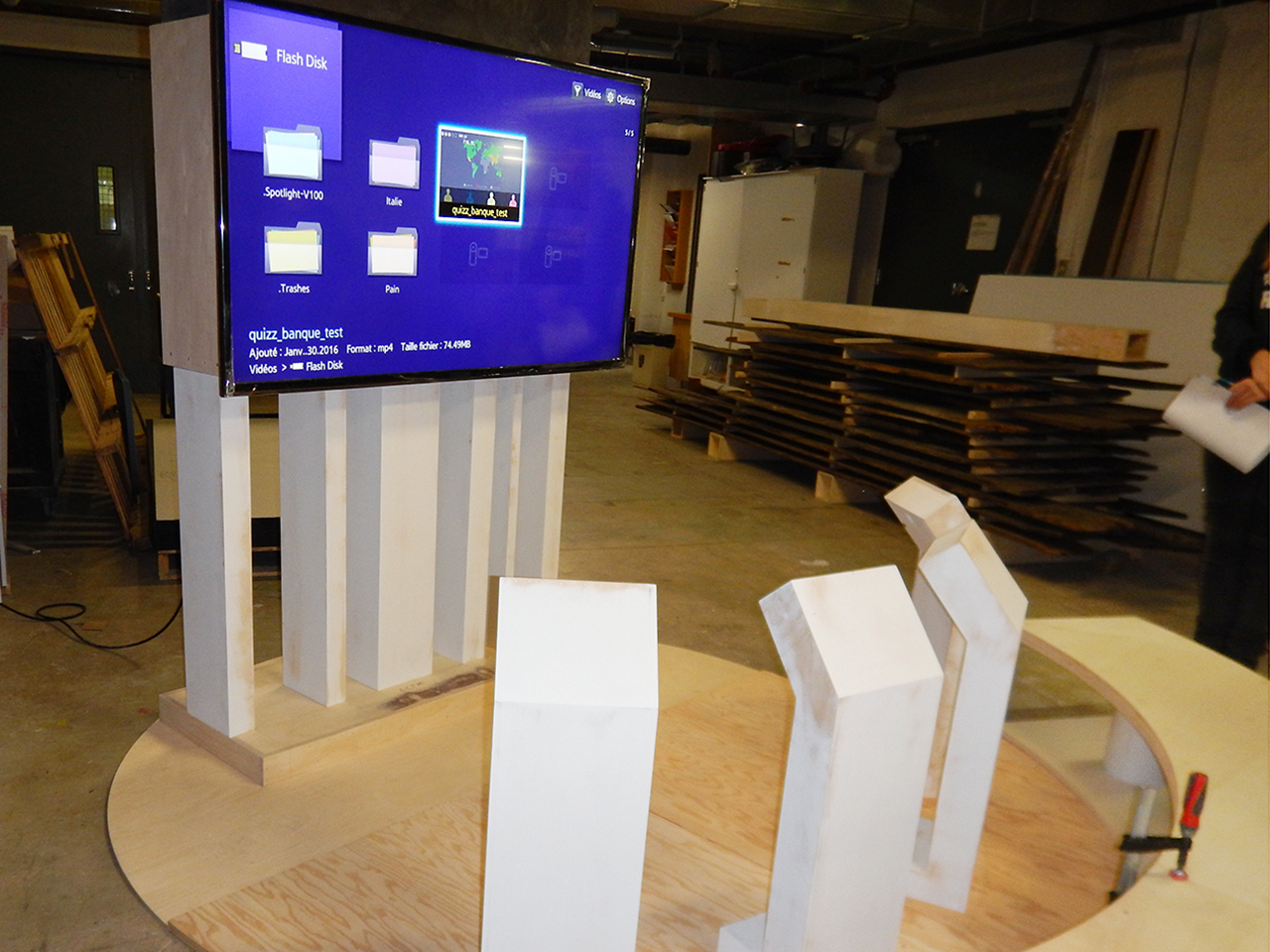 wooden forms and a large monitor in a workshop