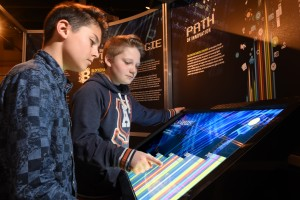 Two boys manipulating a digital touch panel