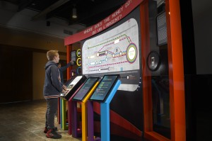 boy standing at a set of touch screens and a large route map