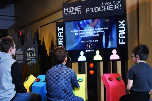 A group of kids sitting in front of a large digital display panel