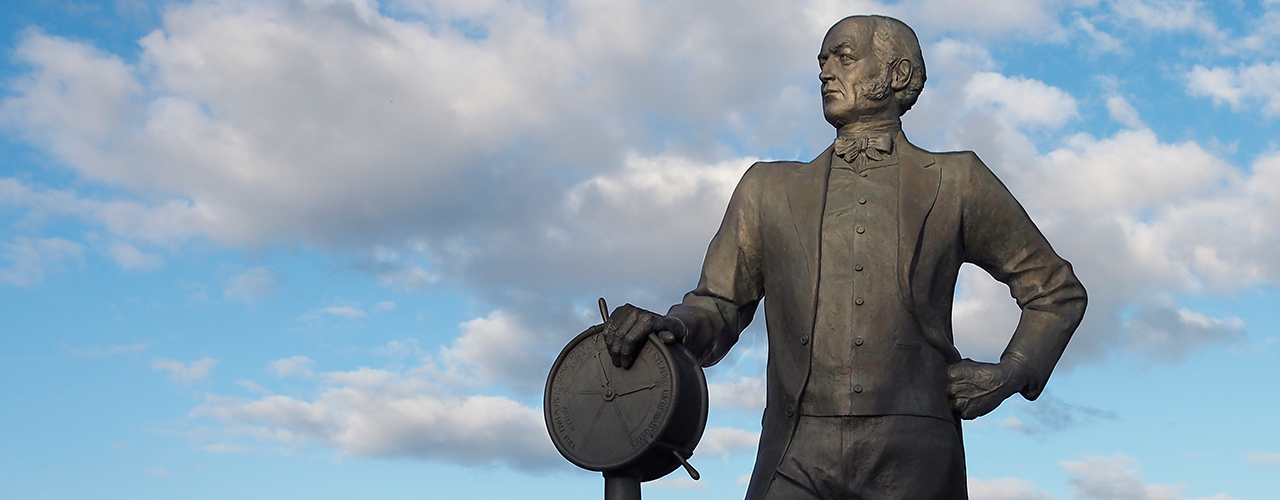 statue of a man with a ship's telegraph control