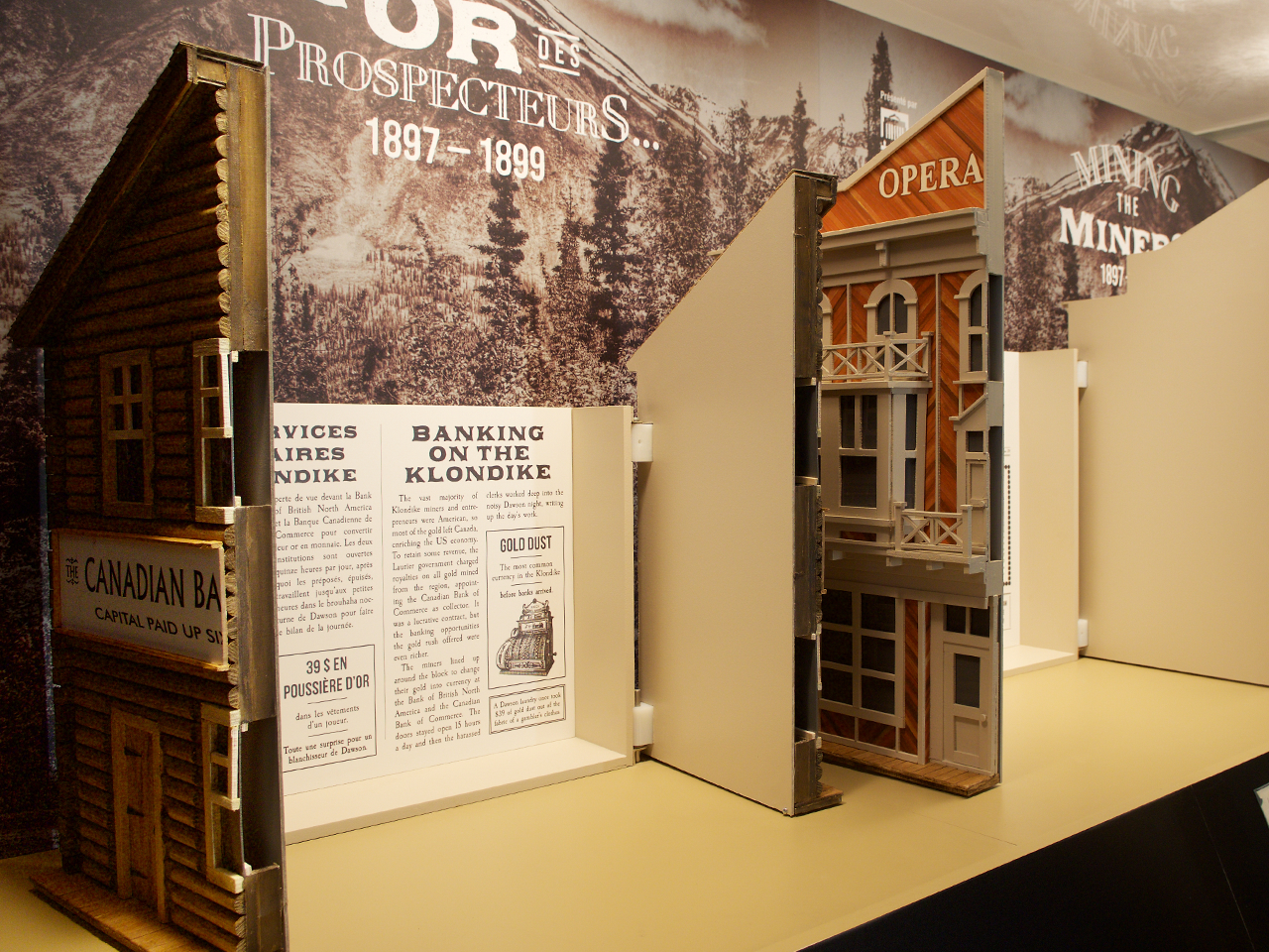 model buildings with the fronts open to reveal museum text