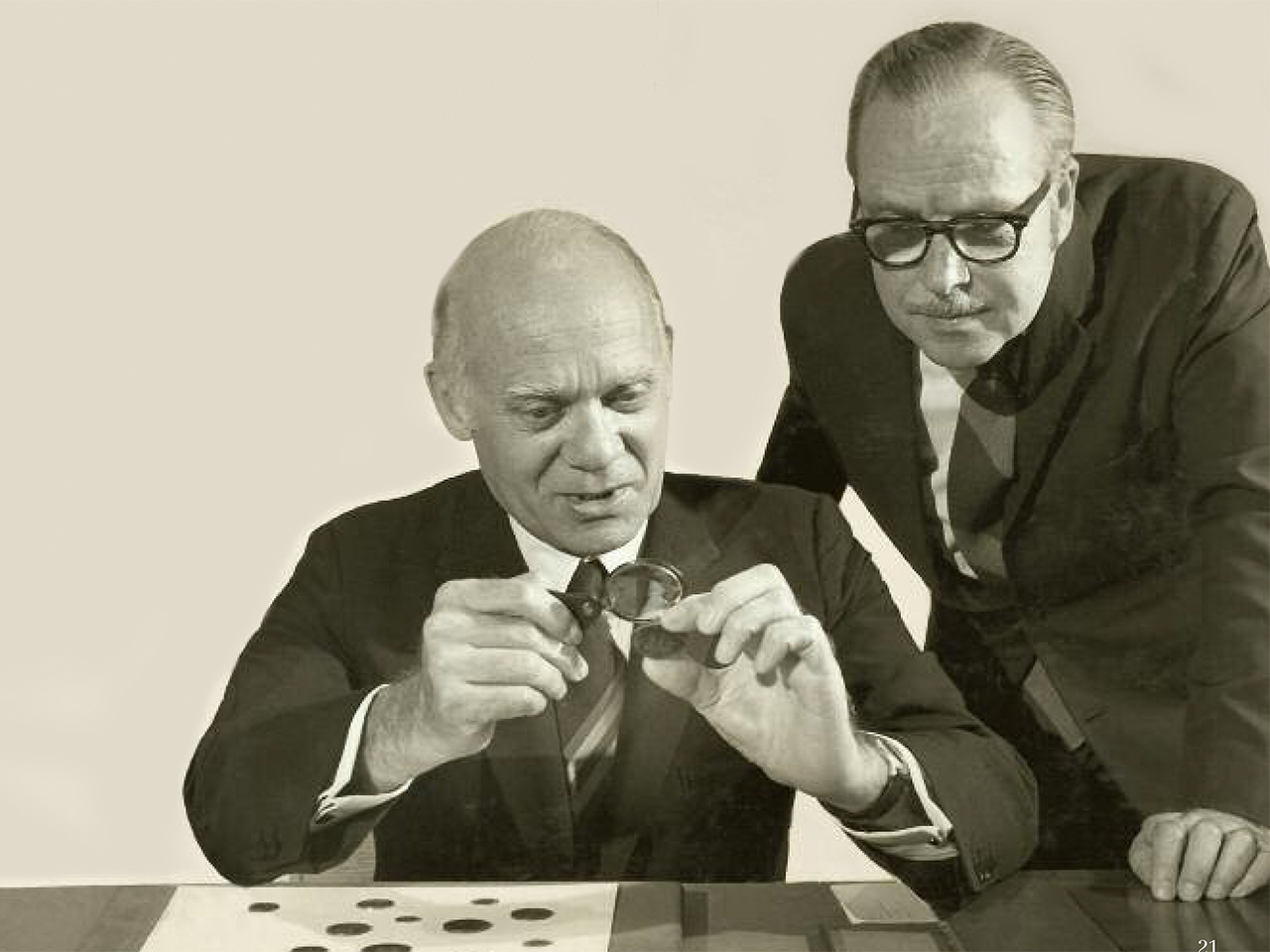 1960s image of two men looking at coins