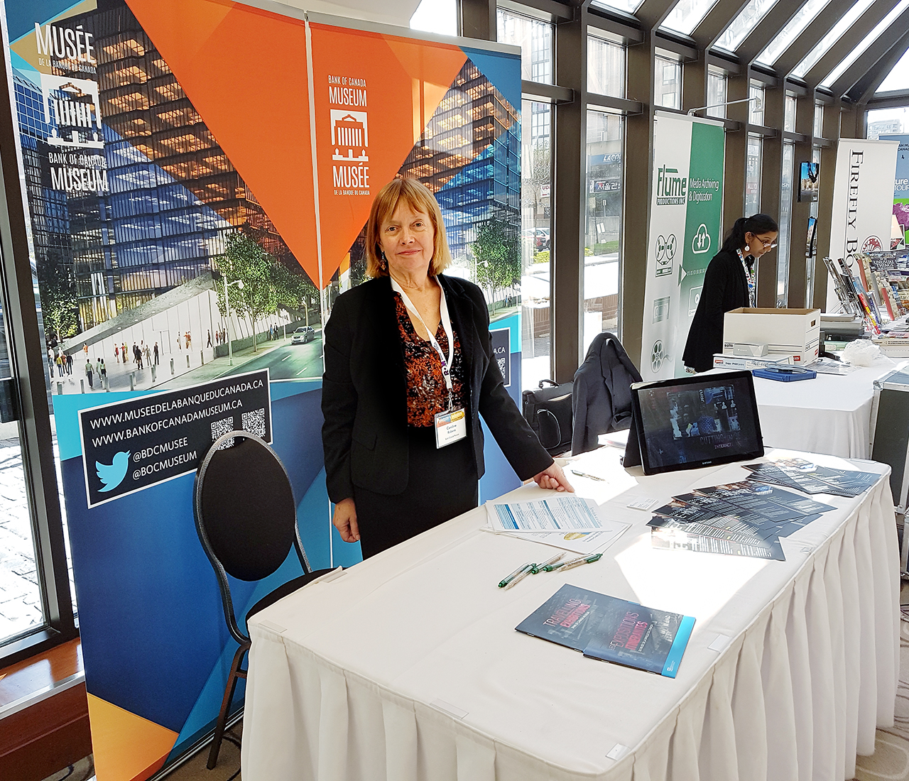 woman standing at a conference kiosk