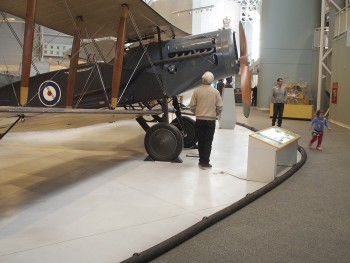 man viewing an aircraft from in front of the barrier