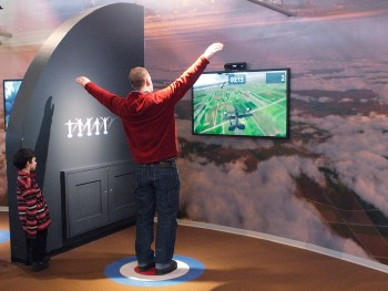 man standing with arms out interacting with a simulation game