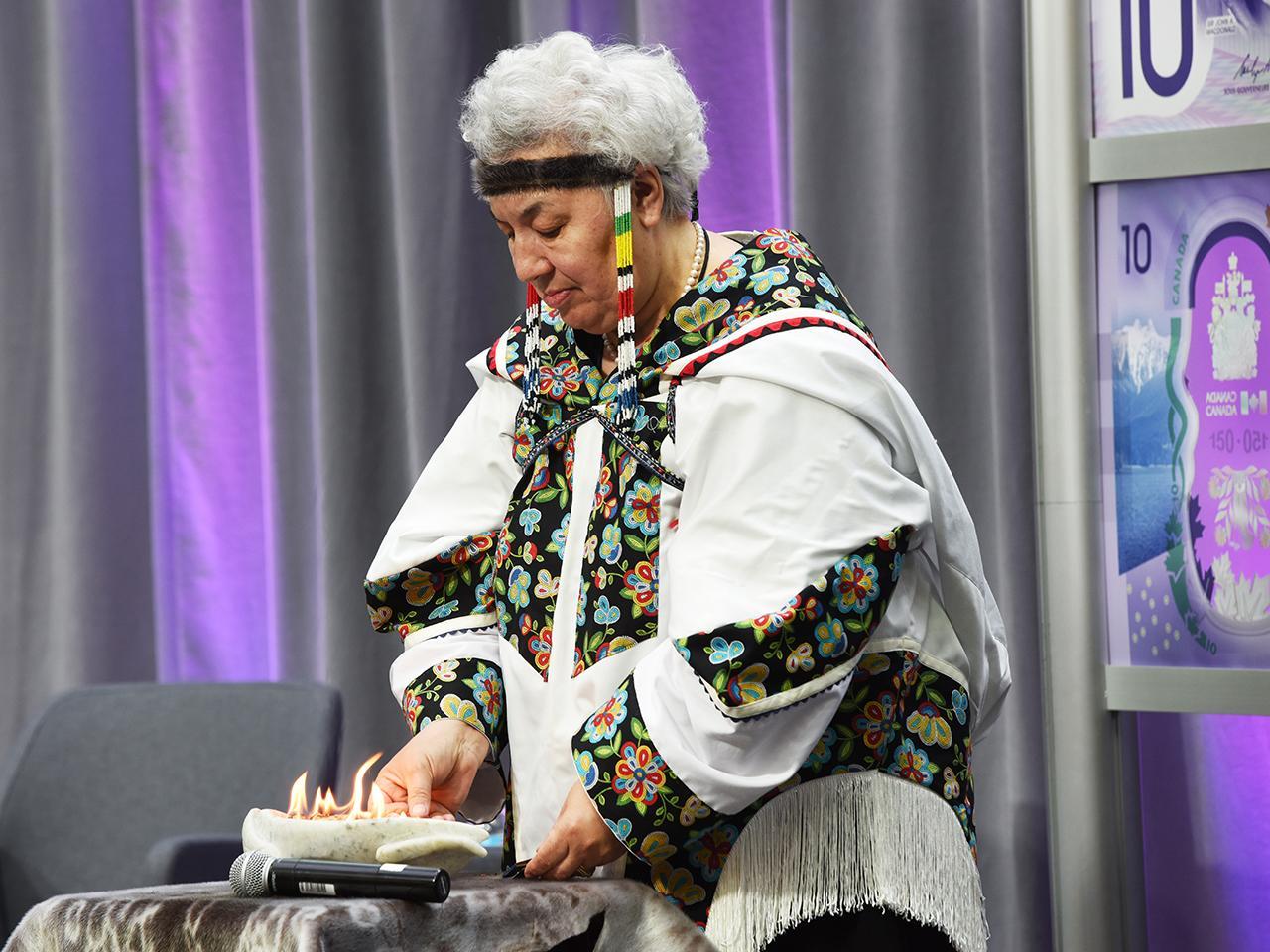 woman lighting an Inuit lamp