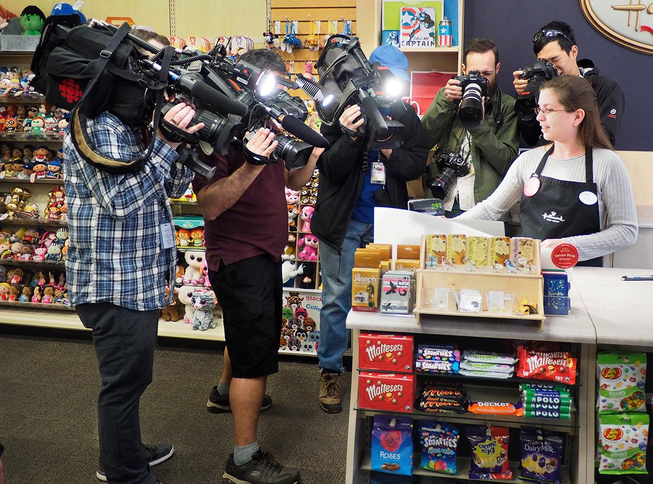 photographers and videographers crowd a store clerk