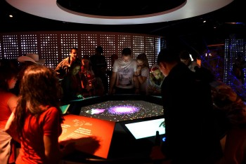 crowd gathered around a big digital table