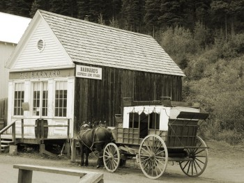 wooden building with wagon and horses
