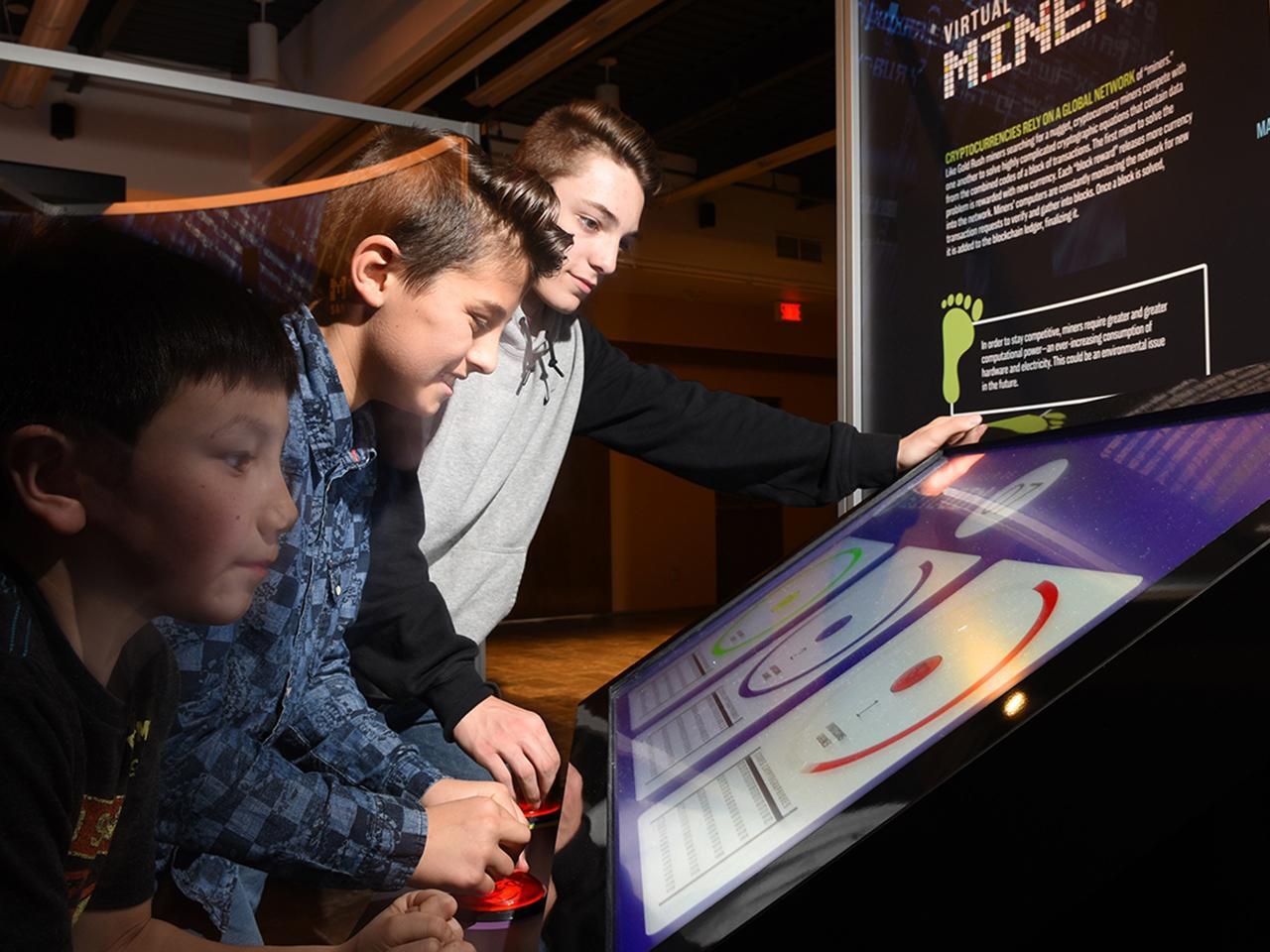 three boys at a video game terminal