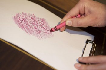 hands making a crayon rubbing of a coin