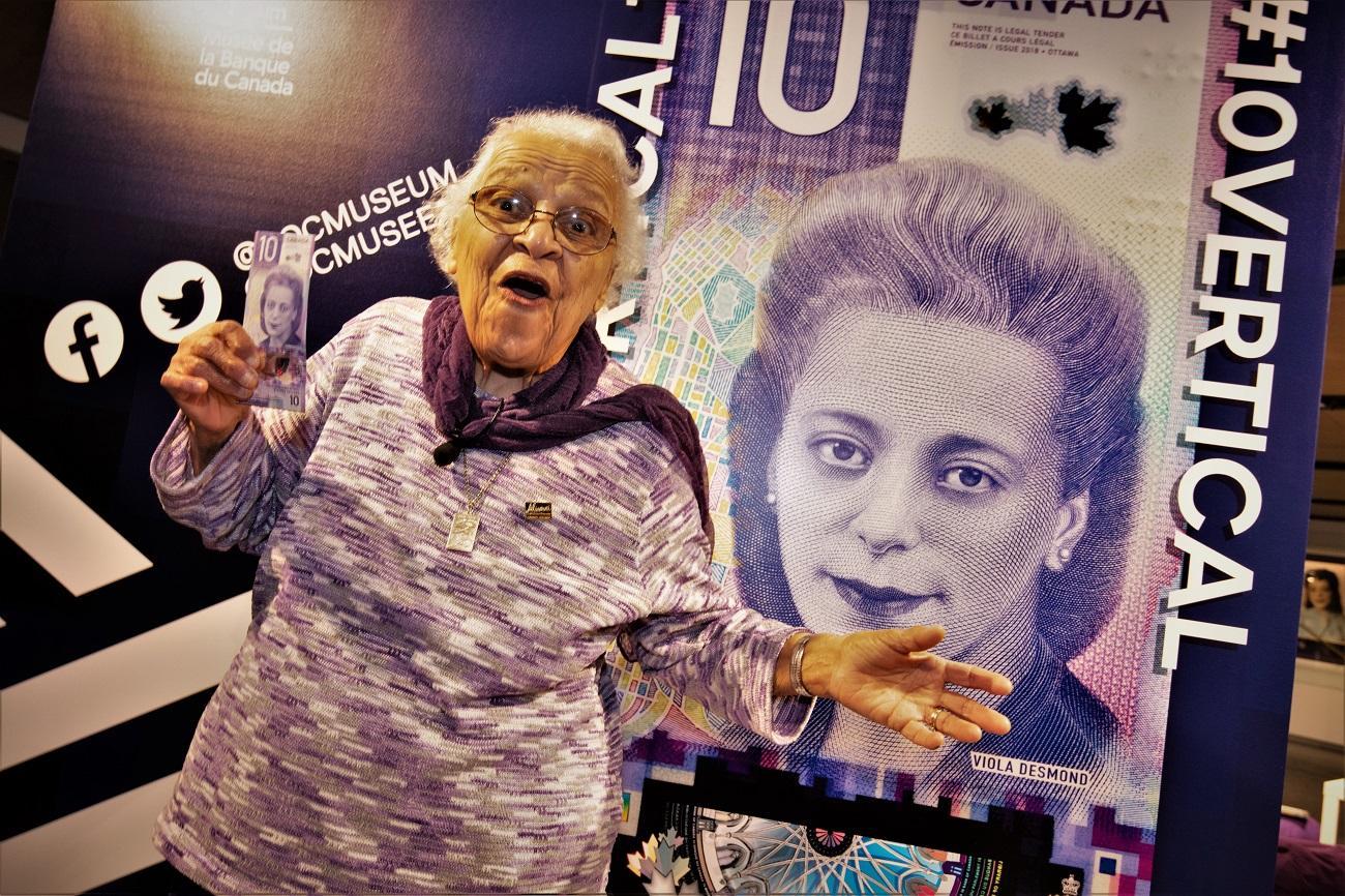 Wanda Robson, holding a new $10 bill