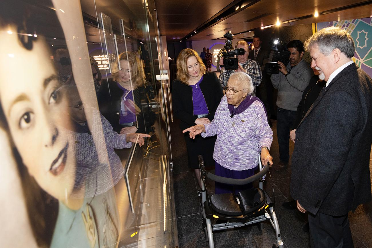 Wanda Robson looking at a museum display of Viola Desmond