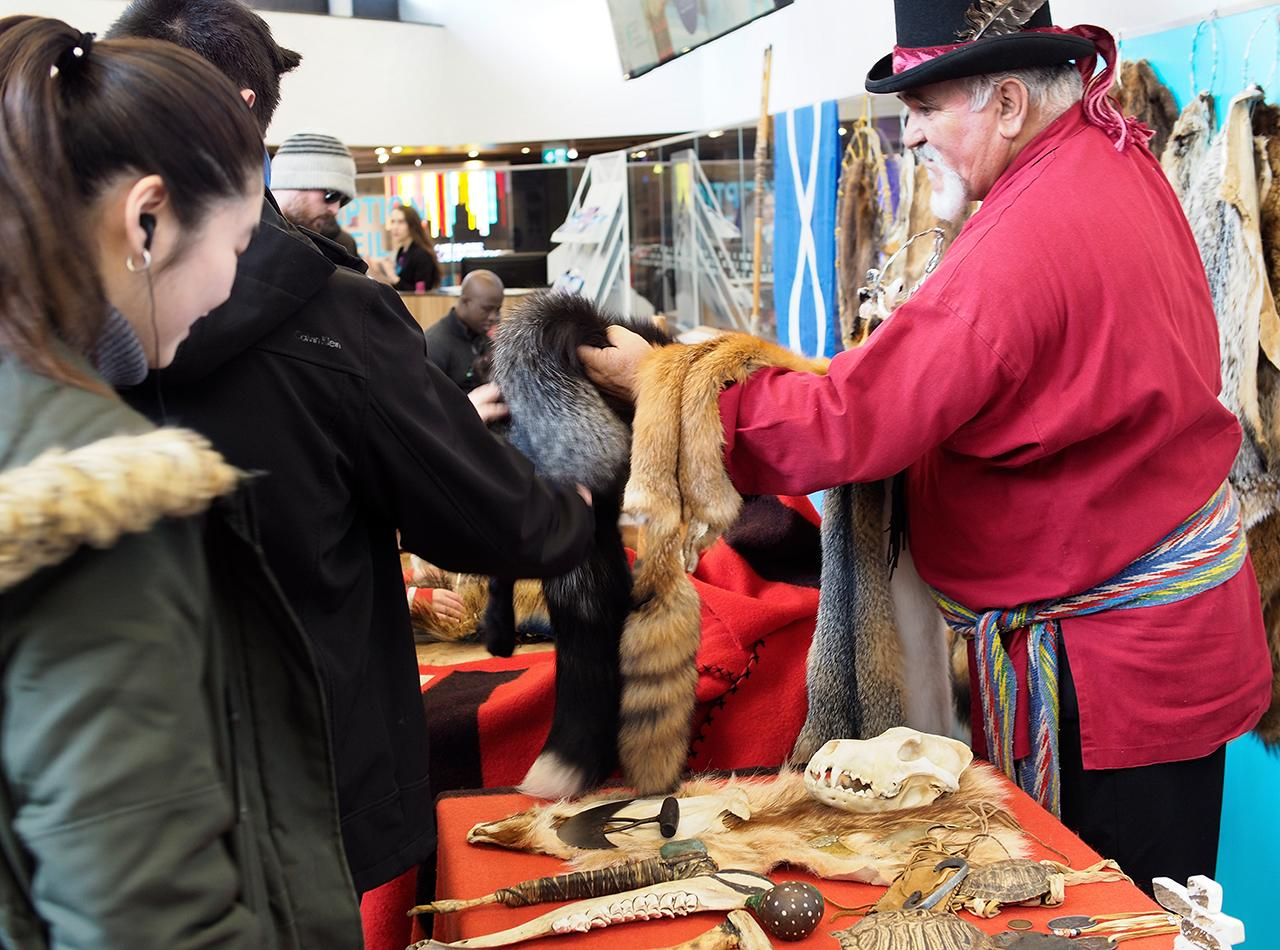 man showing furs to visitors