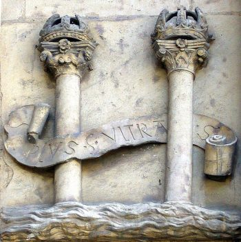 stone carving of two pillars with ribbon around them