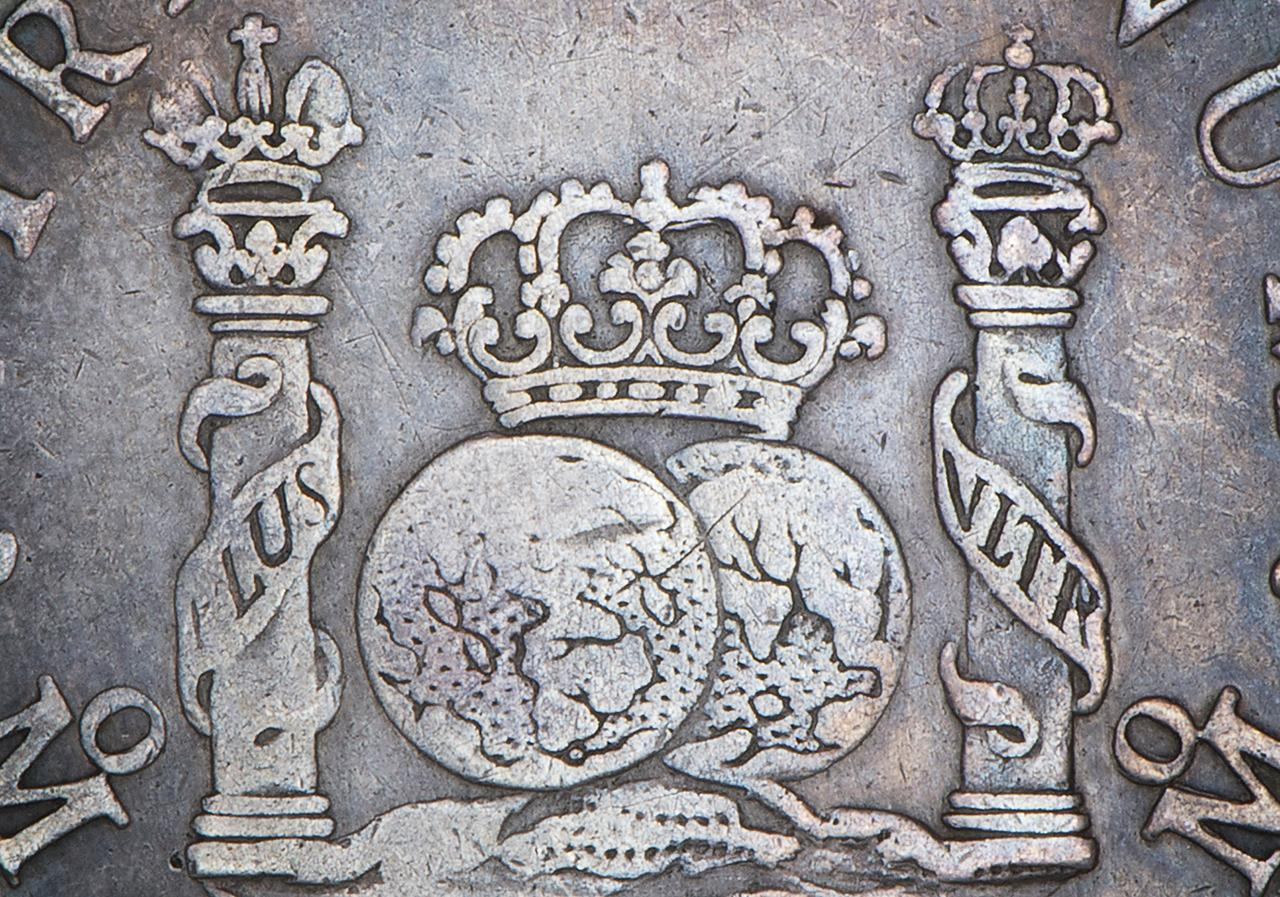old coin showing pillars, globes and crowns