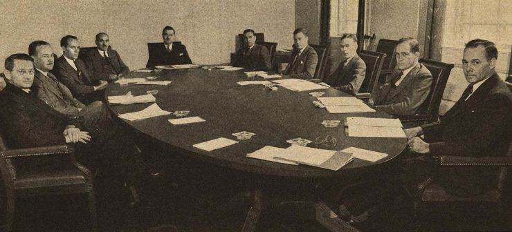 black and white image of men around a boardroom table