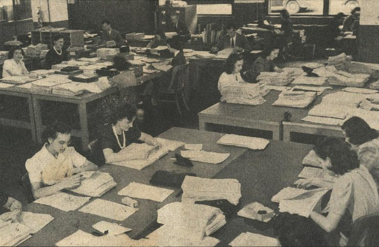 newspaper image of dozens of women working in an open office