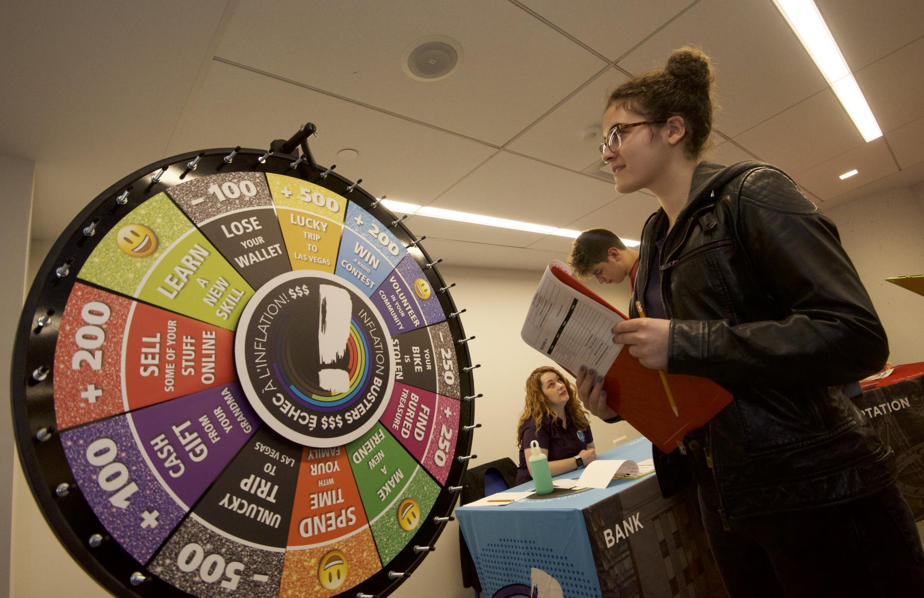 a student spins the wheel of chance in the school program Inflation Busters