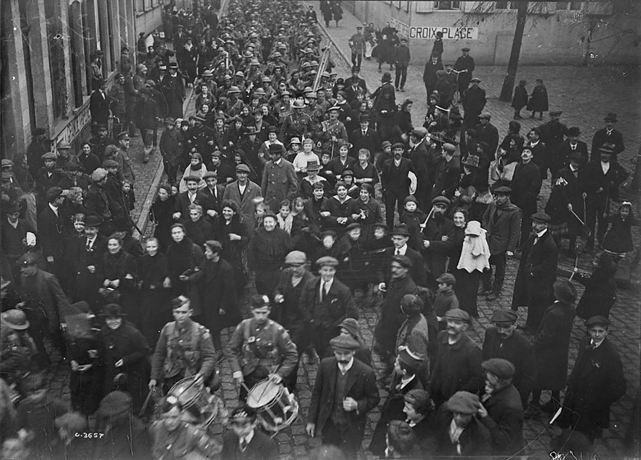 old photograph showing crowds and marching soldiers