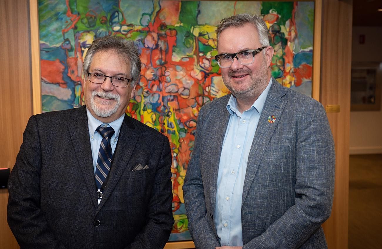 portrait of two men standing in front of a painting