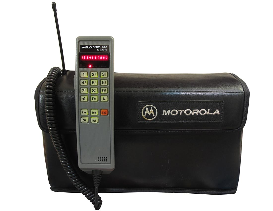An early mobile phone receiver and its big carrying case.