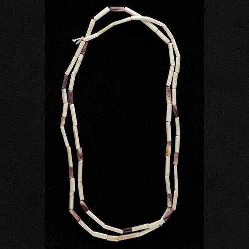 Wampum bead string with long, cylindrical shell beads in beige and light purple or brown. Looks like a necklace.