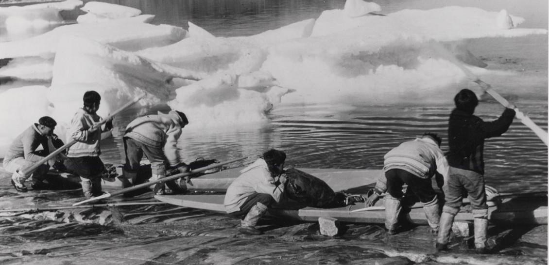 Black and white photo of six Inuit men loading kayaks.