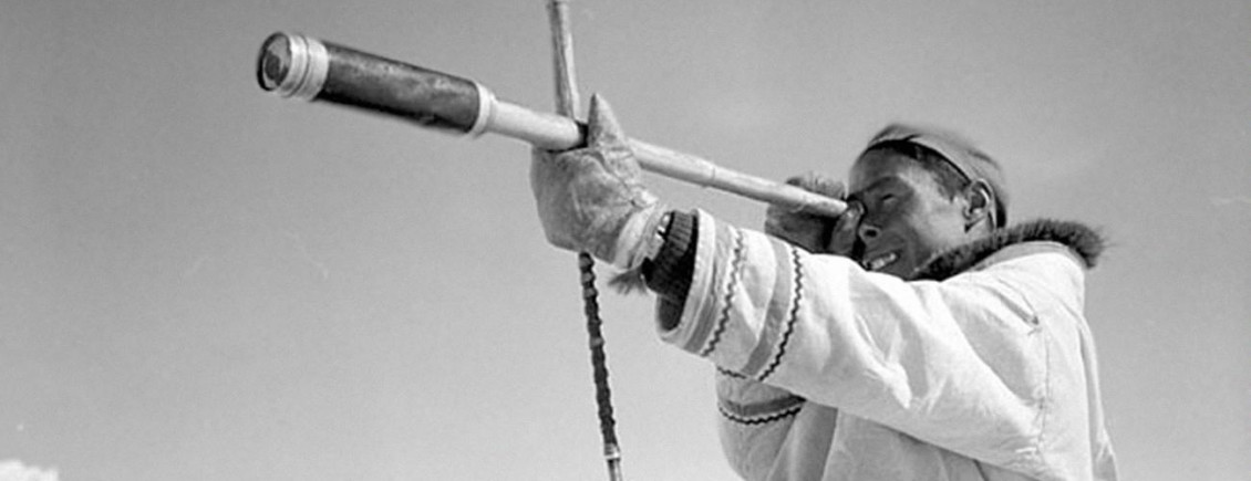 Black and white photo of an Inuit hunter looking through telescope.