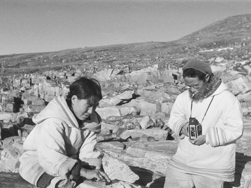 Black and white photo of Inuit man photographing a woman scraping a hide.