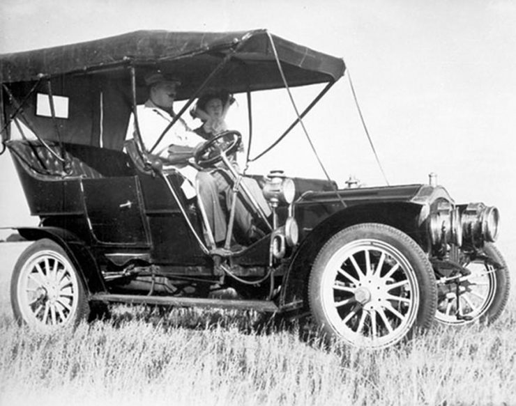 A black and white photo of a car from before the First World War in a field.