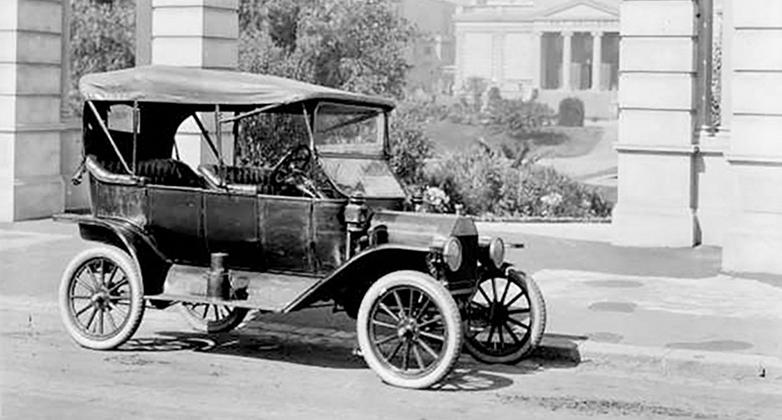 A historic photo of a car from before the First World War parked in front of public buildings.