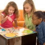 A diverse group of 4 young children playing a board game.