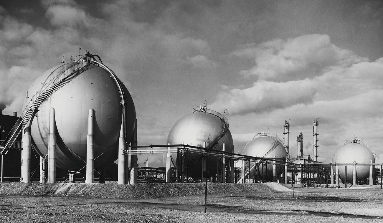 Photo, black and white, a series of huge, silver spheres with smokestacks behind.