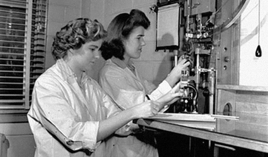 Photo, black and white, two white-coated young women working in a laboratory.