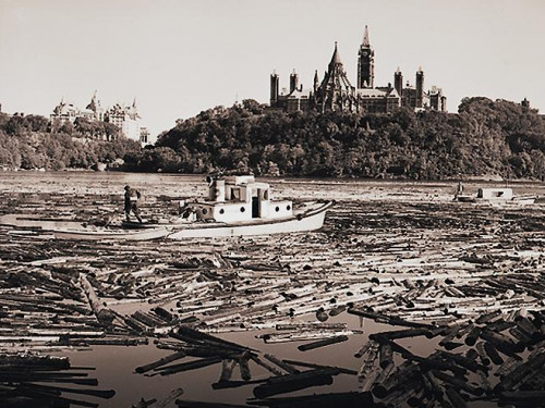 Photo, black and white, thousands of logs and two boats on a river in front of a hill with gothic towers and trees.