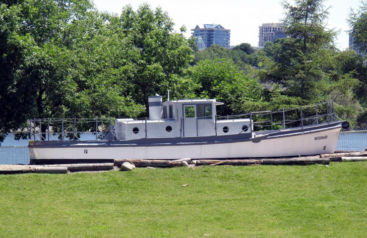Photo, colour, small white boat with a cabin and smokestack, sitting on land in a park setting.