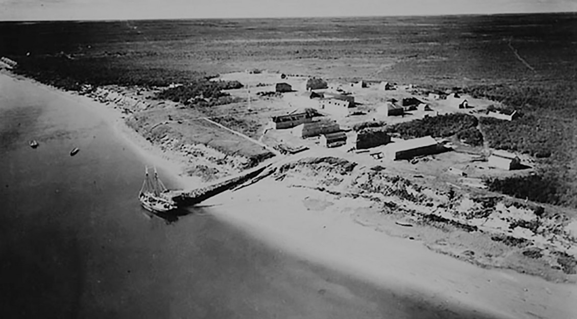 Photo, black and white, aerial view of vast empty land with military-style settlement on a bay.
