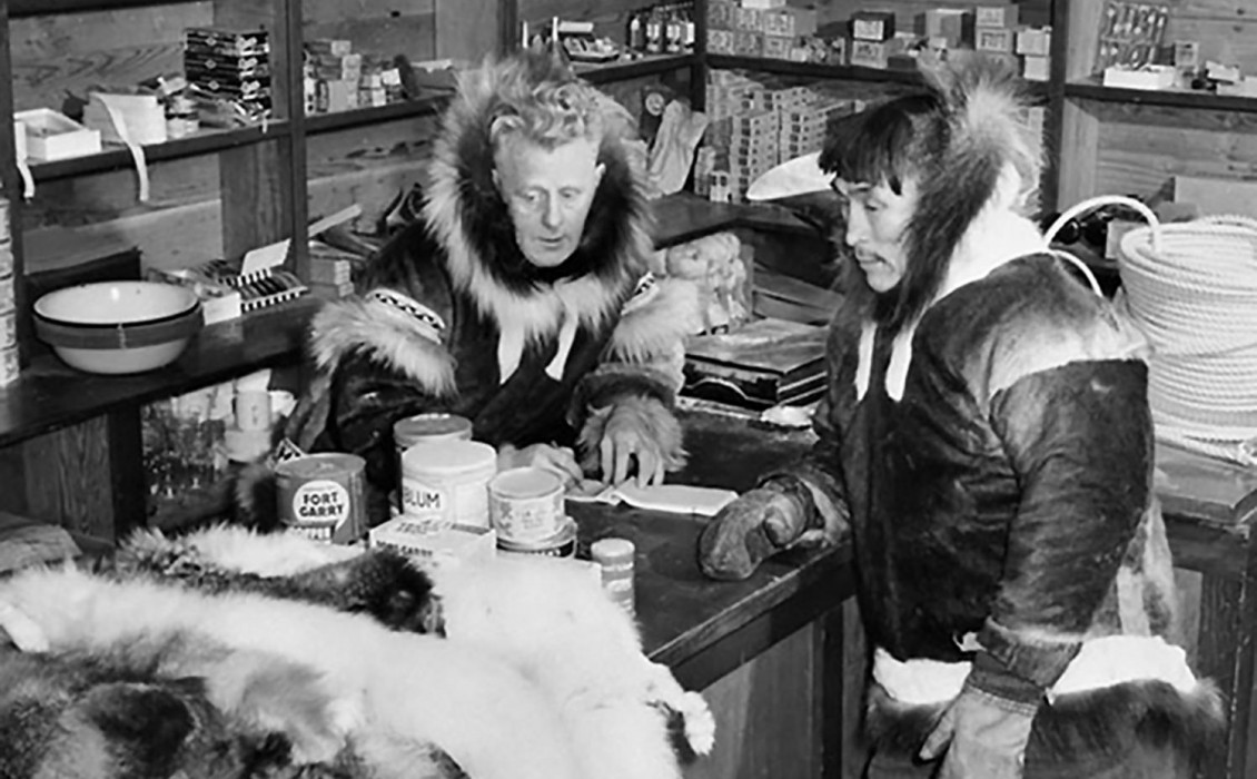 Photo, black and white, white man and Indigenous man wearing parkas in a room stocked with domestic supplies.
