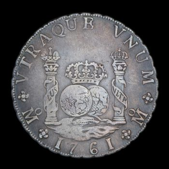 Silver coin of 8 reales, reverse side showing 2 pillars wrapped in banners and 2 globes topped with a crown.