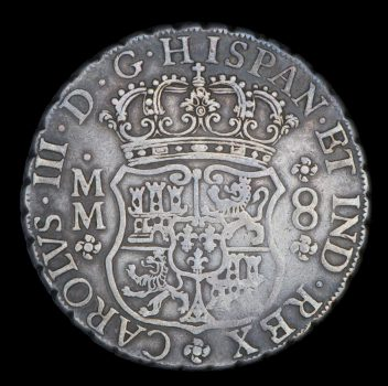 Silver coin of 8 reales, obverse side showing coat of arms of Spain crown and Latin script.