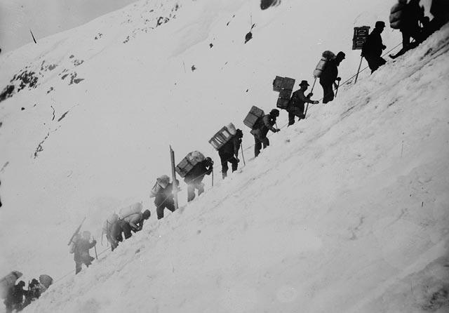 Photo, black and white, a line of men wearing large backpacks and climbing a snowy mountain.