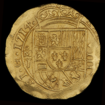 Coin, gold, roughly round, Latin text at the edges and off-centred surrounding a crowned coat of arms.